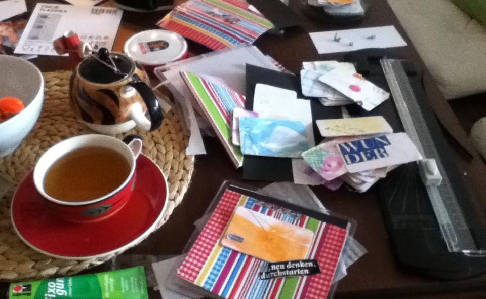 Auf diesem Foto sehen Sie eine kreative Teepause mit diversen Karten, Schnipseln und allem was man noch so wunderbar verwerten kann