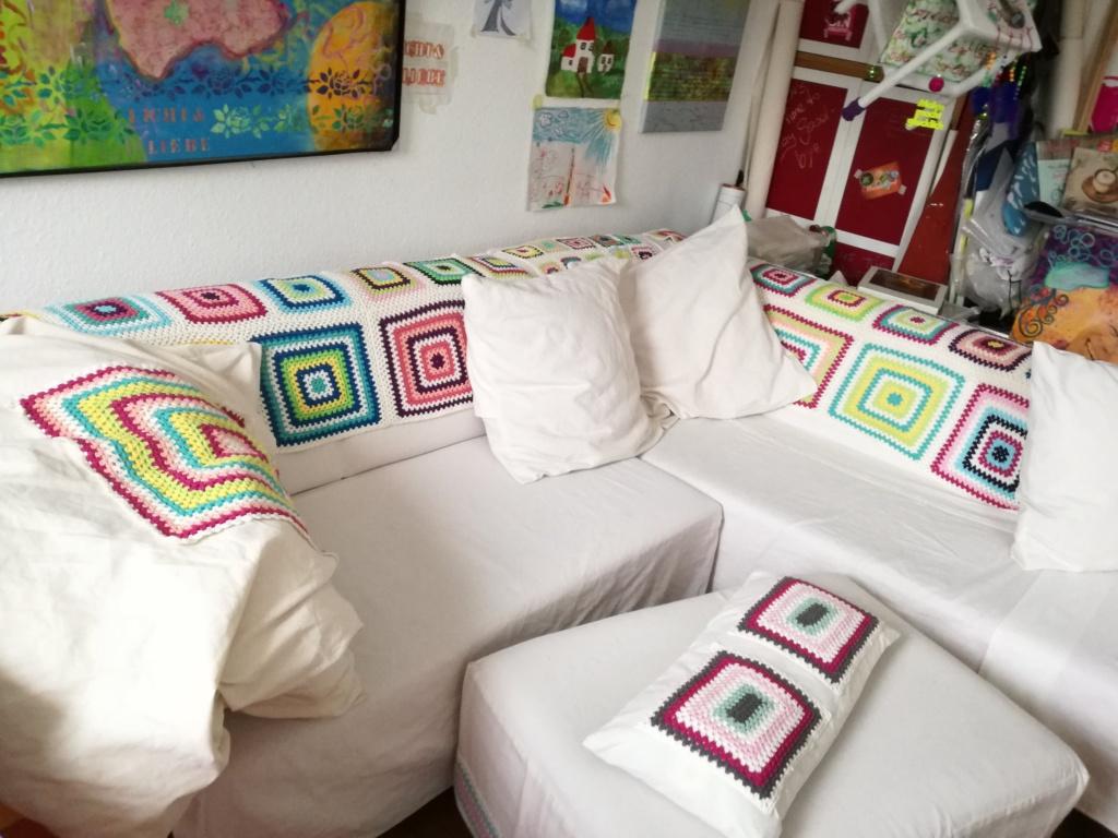 Das Bild zeigt ein Sofa mit Granny-Squares